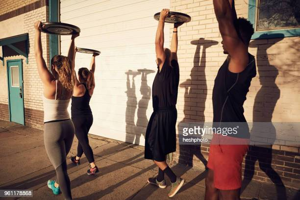 group of people with arms raised carrying weights equipment, side view - heshphoto stockfoto's en -beelden