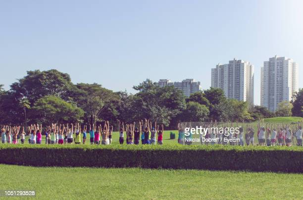 group of people with arms raised exercising on field against clear sky in city - curitiba stock pictures, royalty-free photos & images