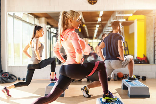 Group of people with healthy habits doing exercises for legs on steppers. Gym interior. 1127583087