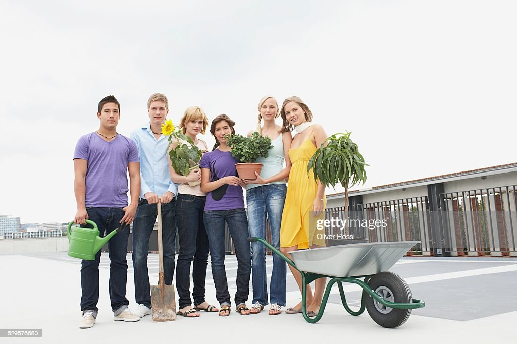 Group of People with Potted Plants and Wheelbarrow : Stockfoto