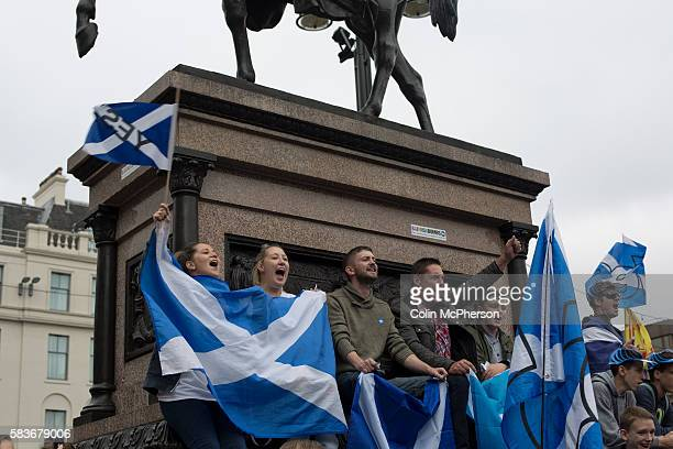 A group of people with Scottish saltire flags sitting on a statue at a proindependence gathering in George Square Glasgow The gathering brought...