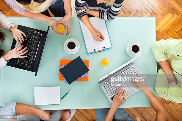 Group of people with two laptops at a meeting