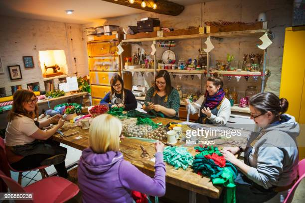 group of people, women around a table in workshop, making paper flower wreaths. - craft stock pictures, royalty-free photos & images