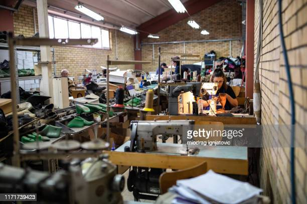 group of people working in a shoe factory - shoe factory stock pictures, royalty-free photos & images