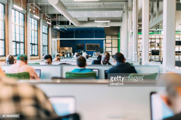 group of people working in an open plan business. startup. bring your own device area. - área sem divisões imagens e fotografias de stock