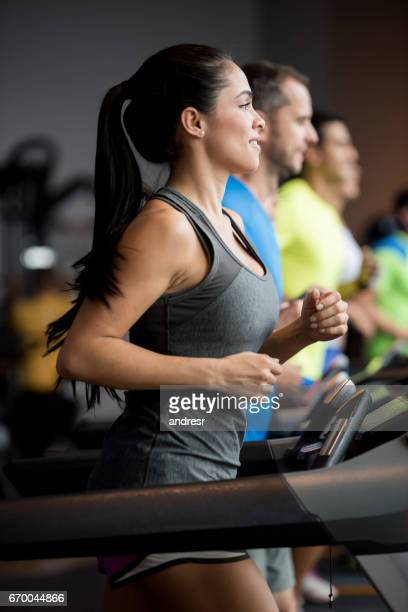 Group of people working out at the gym running in the treadmills
