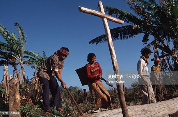 A group of Phnong farmers work on their land in northeastern Cambodia In the foreground is a wooden cross planted to bless the land A small group of...