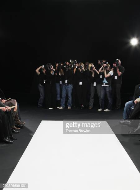 group of photographers in front of catwalk at fashion show - fashion show stock pictures, royalty-free photos & images