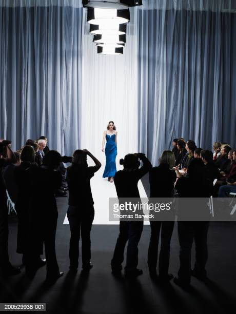 group of photographers in front of female model walking down catwalk - catwalk stock pictures, royalty-free photos & images
