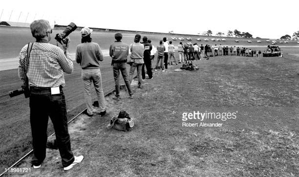 A group of photographers line the track at the Daytona International Speedway to capture the action of the 1988 Daytona 500 on February 14 1988 in...