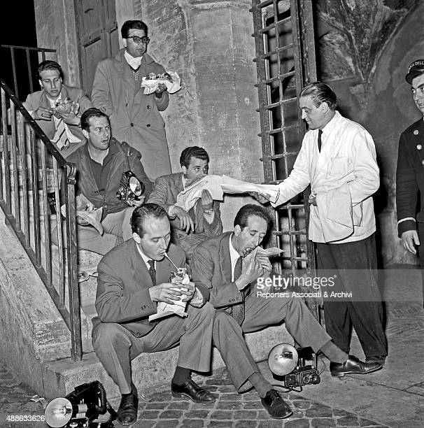 A group of photographers sitting on a staircase waiting for Rainier III Prince of Monaco and his wife American actress and princess Grace Kelly...