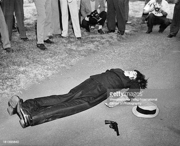 A group of photographers take pictures of a dummy arranged in a crime scene as though killed in a shootout New York New York 1946 Photo by...