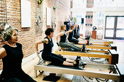 Group of pilates students doing tricep dips on reformers during class in fitness studio - gettyimageskorea