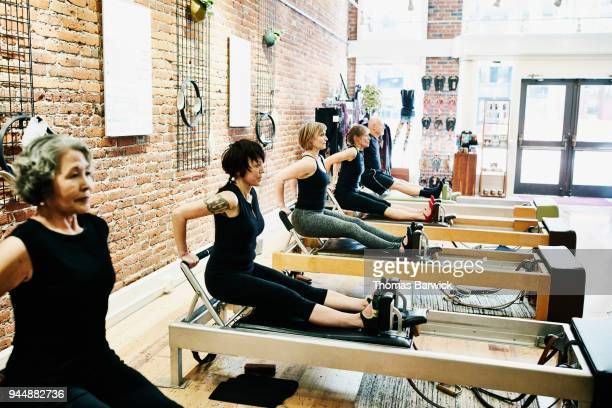 Group of pilates students doing tricep dips on reformers during class in fitness studio