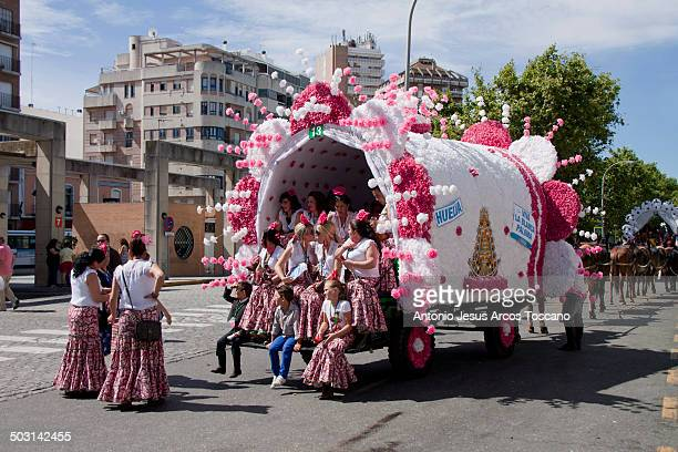 Group of pilgrims dressed in traditional clothing of flamenco, sitting in the wagon decorated for the output of the Brotherhood of El Rocio in Huelva...