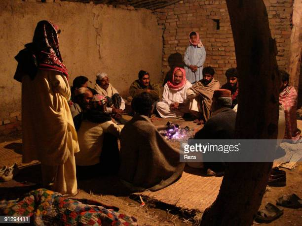 Group of pilgrims gather together by fire near the shrine of Lal shahbaz Qalandar a 13th century Sufi Master worshiped alike by Hindus and Muslims...