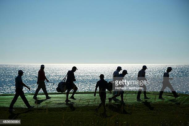 Group of players and caddie leave a tee box during a practice round prior to the 2015 PGA Championship at Whistling Straits on August 11, 2015 in...
