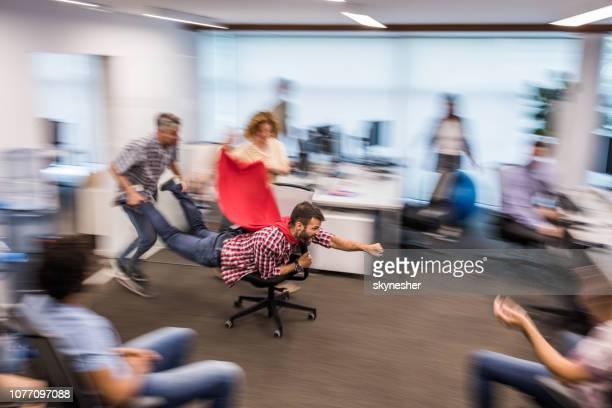 gruppe von verspielten kollegen spaß in bewegungsunschärfe im casual büro. - pause machen stock-fotos und bilder