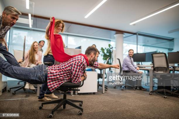 group of playful colleagues having fun on a break at casual office. - superhero stock pictures, royalty-free photos & images