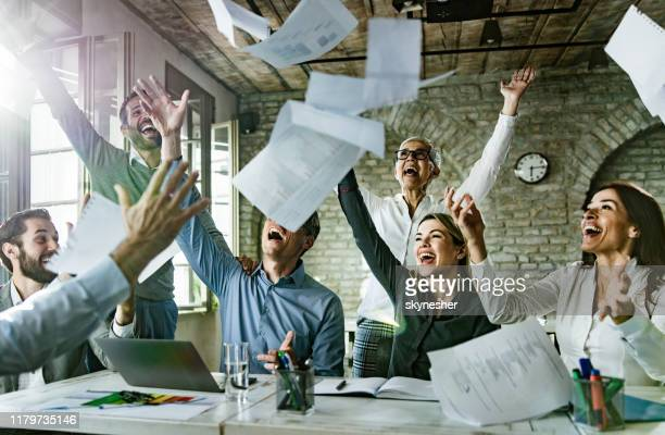 group of playful entrepreneurs having fun while throwing paperwork in the office. - good news stock pictures, royalty-free photos & images