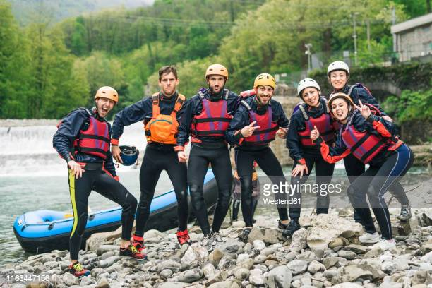group of playful friends at a rafting class posing at boat - ウオータースポーツ ヘルメット ストックフォトと画像
