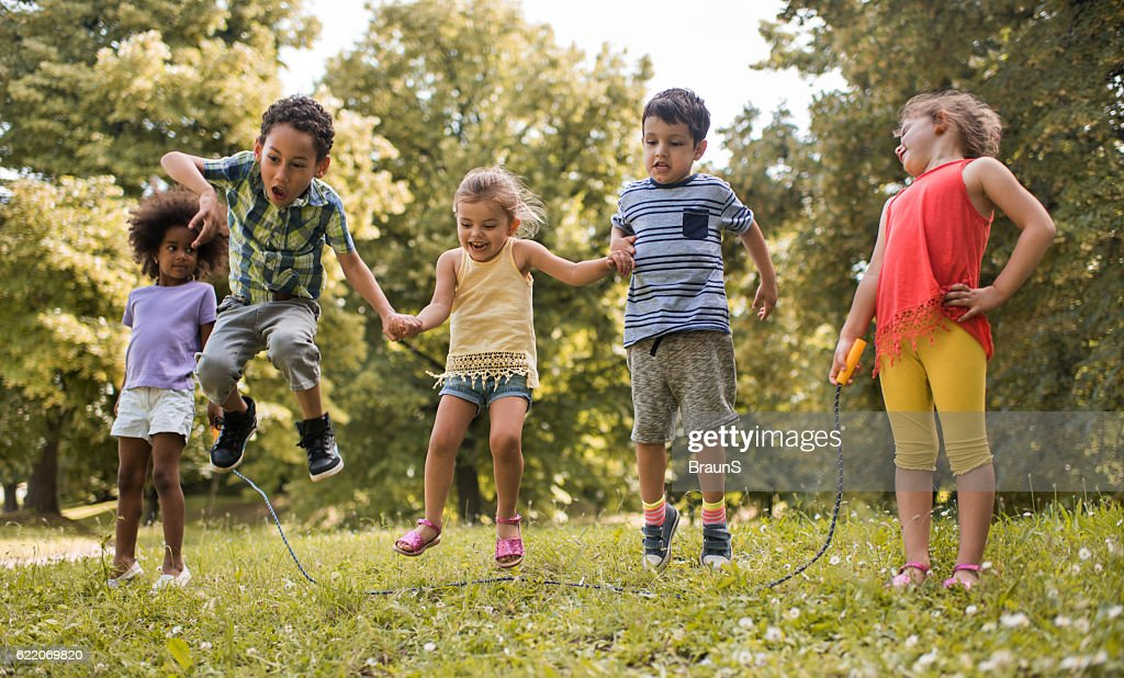 Group of playful kids having fun while skipping jump rope. : Stock Photo
