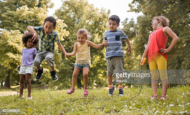 group of playful kids having fun while skipping jump rope. - skipping along stock photos and pictures