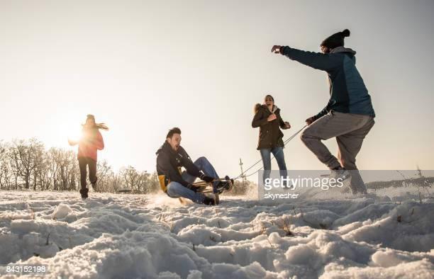 Groep speelse mensen genieten van een dag in de sneeuw.