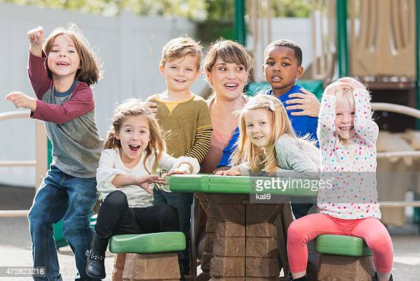 Group of playful preschoolers with teacher having fun