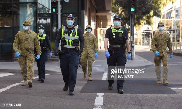 Group of police and soldiers patrol the Docklands area of Melbourne on August 2 after the announcement of new restrictions to curb the spread of the...