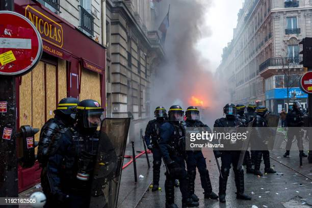 A group of police officers protect access to a street where a truck has been burned by radical groups during the first day of an indefinite general...