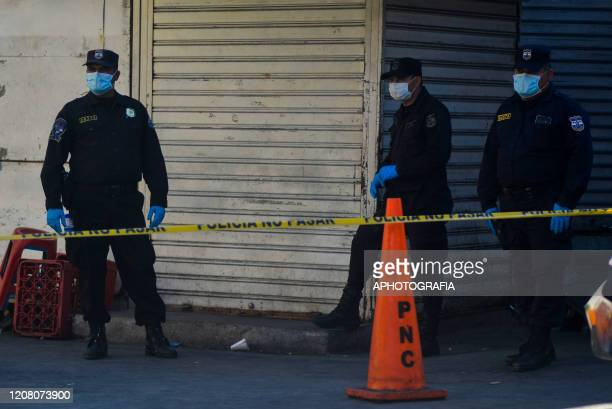 A group of police officers wearing protective masks guard a check point on March 23 2020 in San Salvador El Salvador Three cases of COVID19 have been...