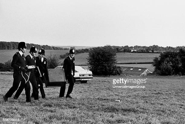 Group of policemen carrying a DJ's confiscated equipment from a rave across a field UK 1990's