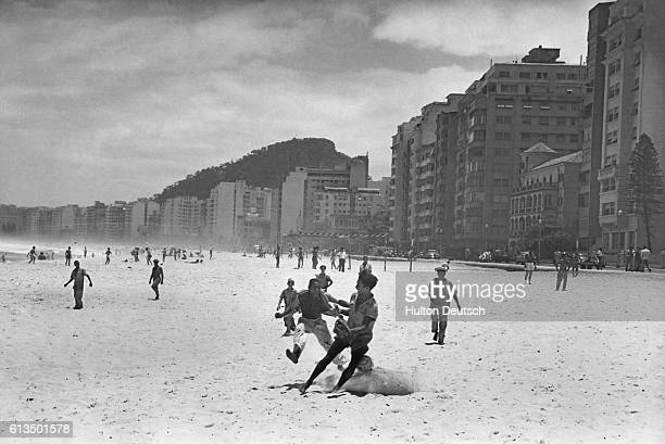 Group of poor workers play soccer on Copacabana Beach, within sight of some of Rio's most expensive housing.