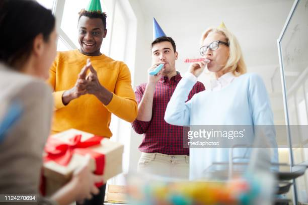Group of positive multi-ethnic employees in party hats standing at table and blowing party horns while congratulating colleague with birthday
