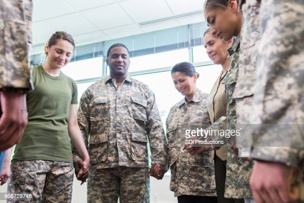 group of praying army soldiers - soldier praying stock photos and pictures