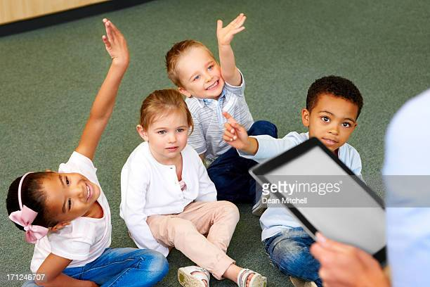 Group of preschool kids in classroom raising hands