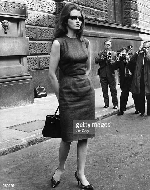 A group of press photographers capture former model and showgirl Christine Keeler on film as she leaves the Old Bailey London where she is one of the...