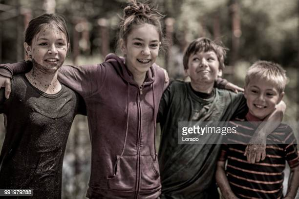 group of pre-teen children having sporty fun at a public mud run obstacle course - military training stock pictures, royalty-free photos & images