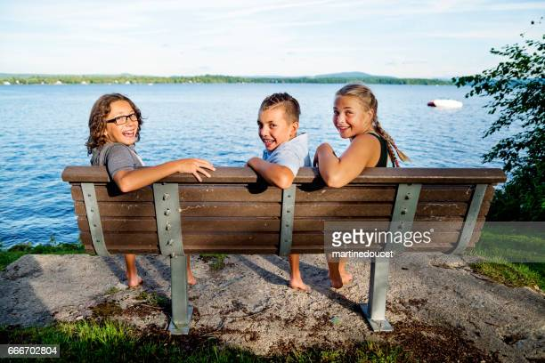 Group of preteen children sitting on bench in front of lake.