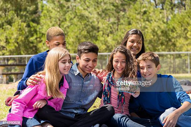 Group of pre-teenage friends take 'selfie' with smart phone.