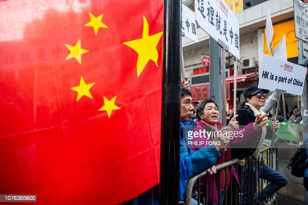 A group of proBeijing protesters chant slogans as people march during the annual New Year's Day prodemocracy rally in Hong Kong on January 1 2019...