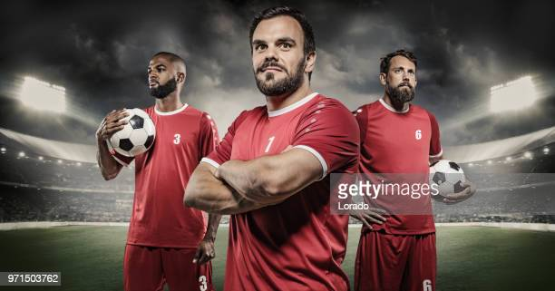 grupo dos jogadores de companheiro de equipe de futebol profissional de adultos posando em um estádio iluminado - camisa de futebol - fotografias e filmes do acervo