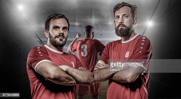 groep van professionele volwassen team stuurman voetballers poseren in een verlichte stadion - voetbalkleren stockfoto's en -beelden