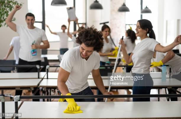 オフィスでプロのクリーナーのグループは、非常に陽気で笑顔を掃除 - ゴム手袋 ストックフォトと画像