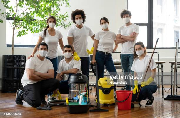 group of professional cleaners working at an office wearing facemasks during the pandemic - crew stock pictures, royalty-free photos & images