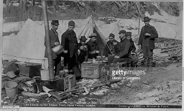 A group of prospectors eat lunch on a crate on the Yukon Trail Alaska 1897 | Location Yukon Trail Dyea Valley Alaska Territory USA