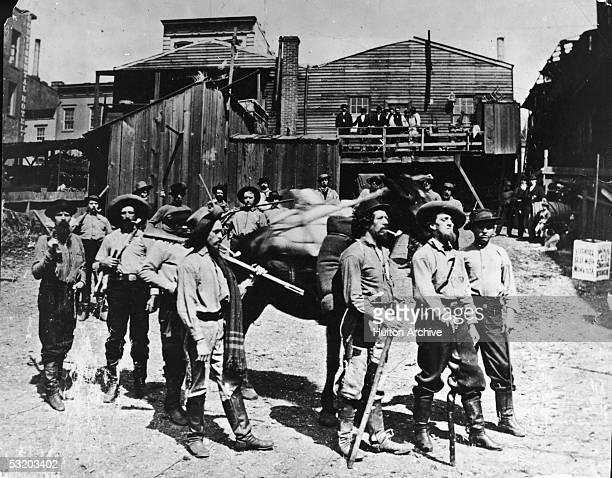 A group of prospectors poses with their equipment and a heavily laden horse as they prepare to go somewhere Northwestern United States 1867