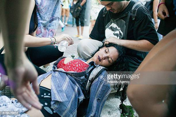 A group of protester take care with a fainted girl during the high school students' protest against cutting and funds deviations committed by the...