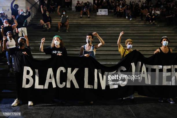 A group of protesters affiliated with Black Lives Matter and other groups congregate in a park and adjoining street outside of City Hall in Lower...